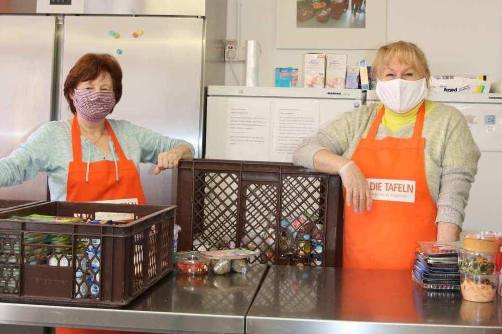 Zwei Mitarbeiterinnen der Tafel stehen hinter einer Theke, auf der sich viele Kisten mit Lebensmitteln stapeln.