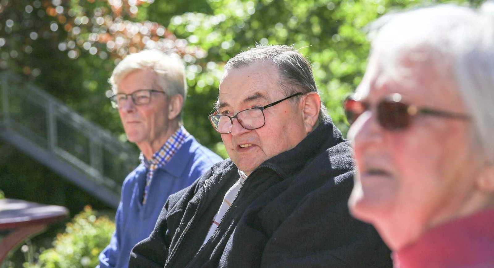 Drei ältere Personen mit Brillen sitzen auf einer Bank im Garten. Im Hintergrund sind Bäume und ein runder Abstelltisch.