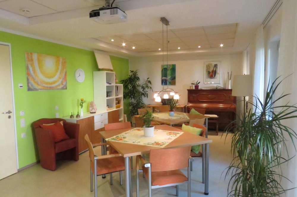 Ein helles Zimmer mit einer Tischgruppe, Sesseln, Zimmerpflanzen und einen Klavier an der Wand.