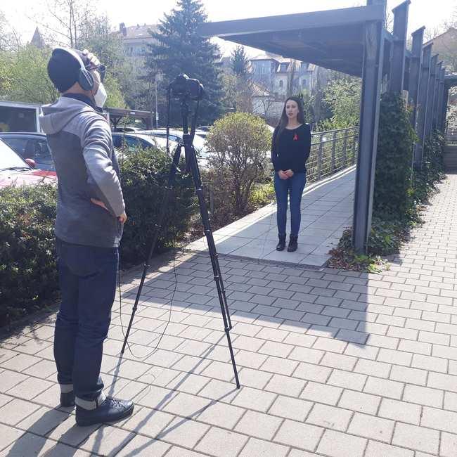 Filmdreh: Eine junge Frau mit roter Aids-Ansteckschleife steht vor einer Kamera. Hinter Kamera und Stativ ein Mann mit Hut.