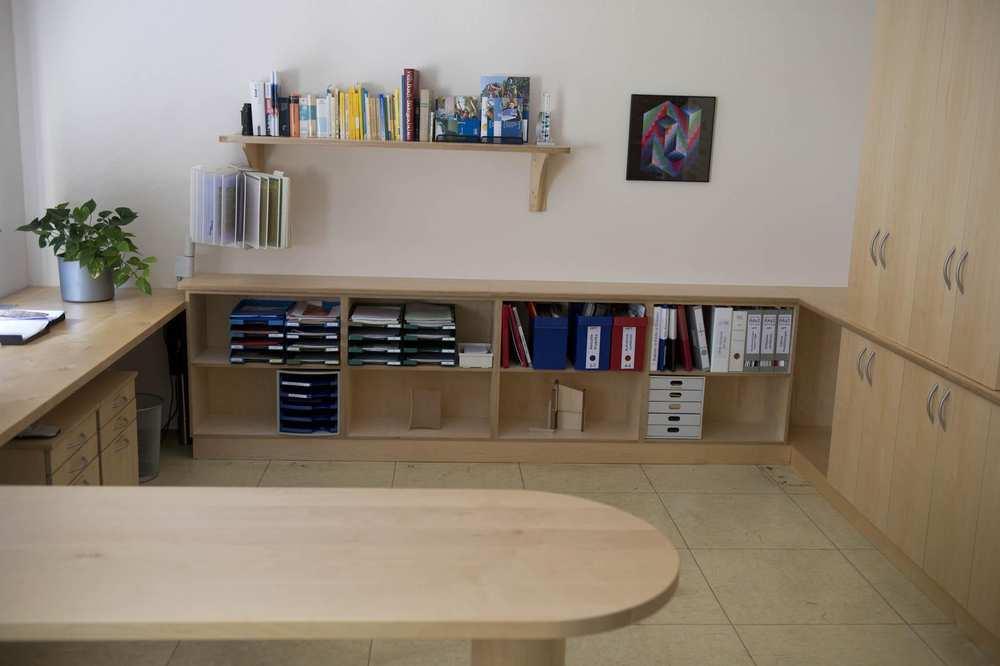 Arbeitsplatten, Bücherregale, Schränke, Schubladen und -fächer aus hellem Holz.