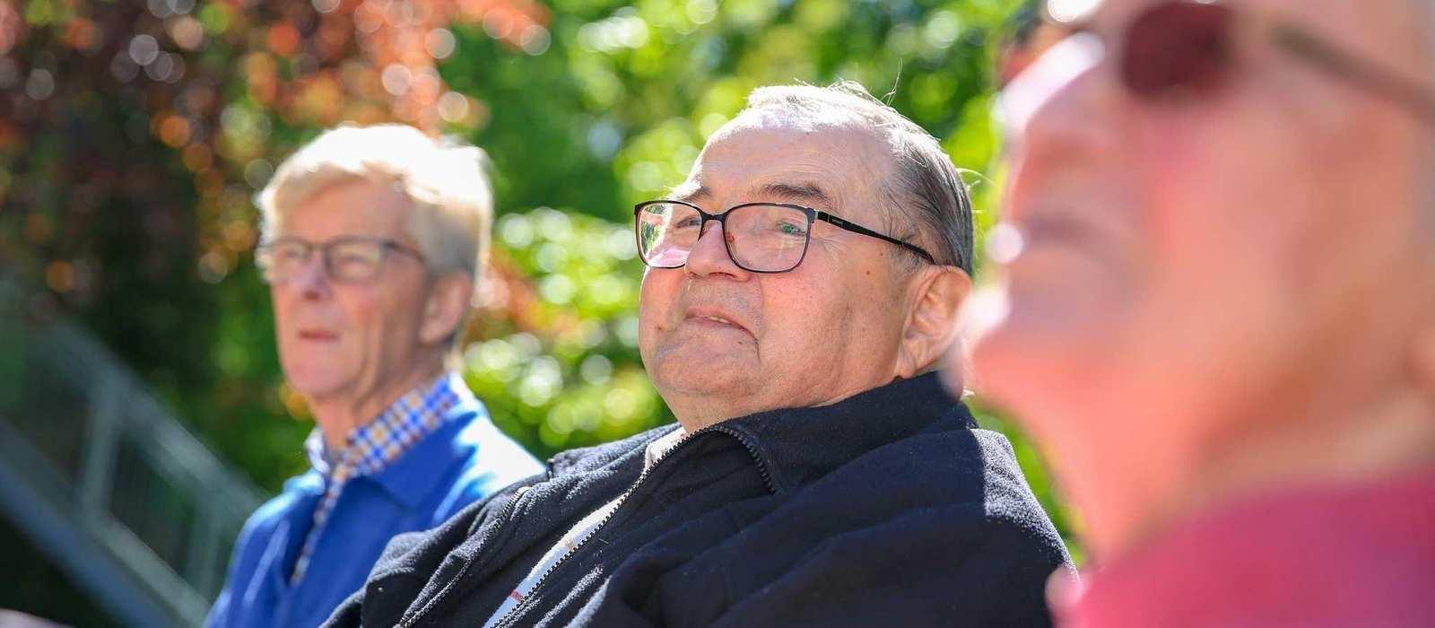 Drei ältere Personen mit Brillen sitzen zusammen auf einer Bank im Garten.