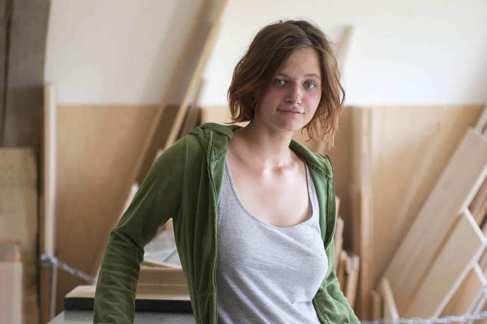 Eine junge Frau mit schulterlangen Haaren. Im Hintergrund sind mehrere Holzbretter.