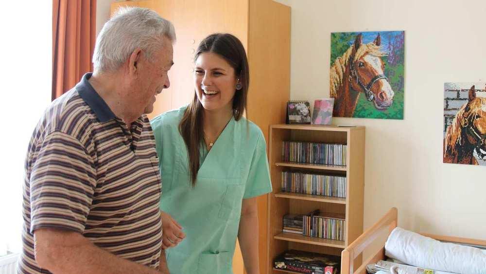 Eine Pflegekraft unterhält sich mit einem Bewohner. Beide lachen.