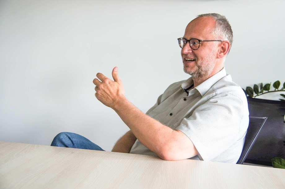 Ein Mann sitzt an einem Tisch. Er spricht und betont das Gesagte mit der Hand.