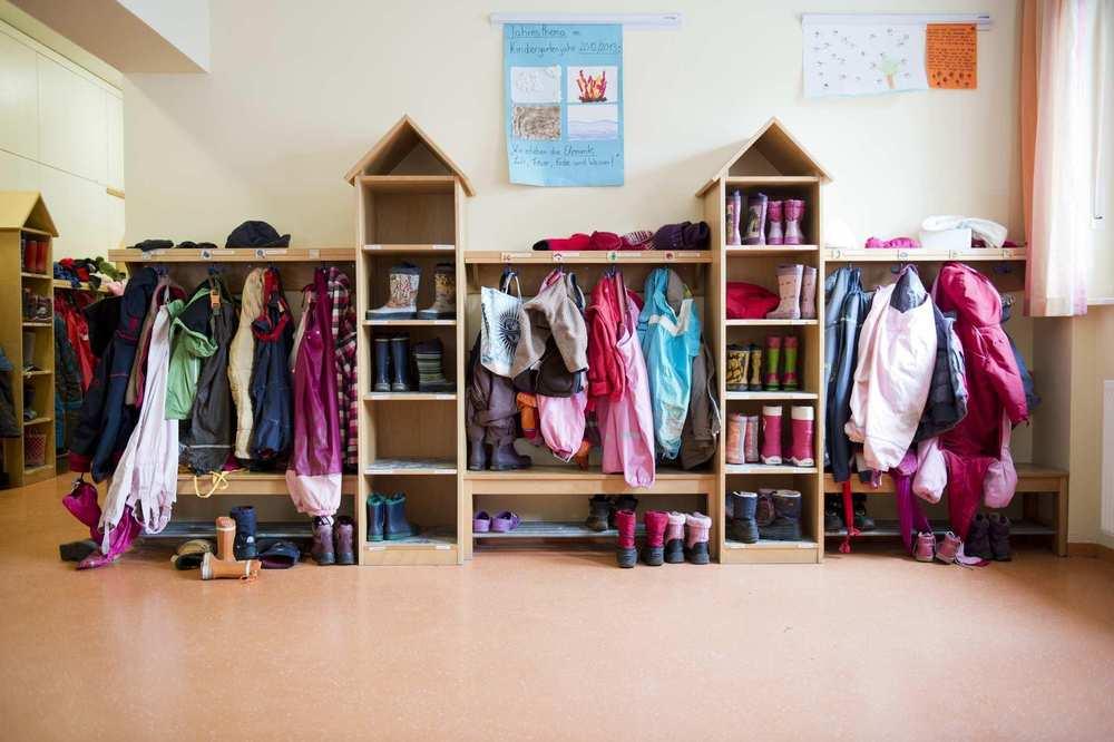 Eine große Garderobe, an der Jacken hängen und auf Ablagebrettern kleine Schuhe stehen. Die Fächer für die Gummistiefel sind als Türmchen angeordnet und haben ein kleines Holzdach.