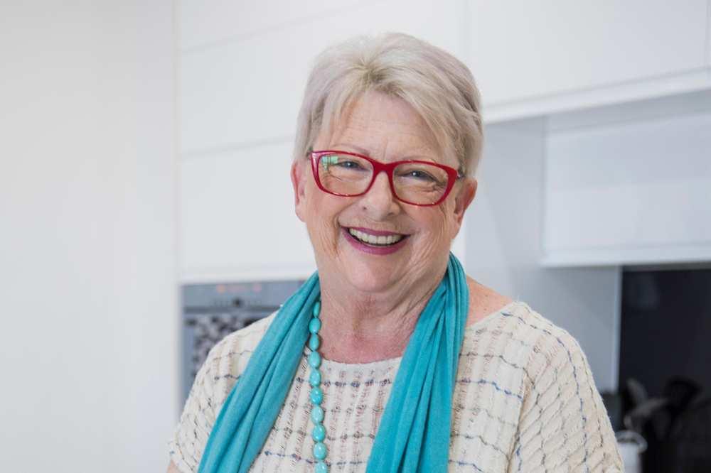 Eine ältere Frau mit Brille und einem blauen Schal.