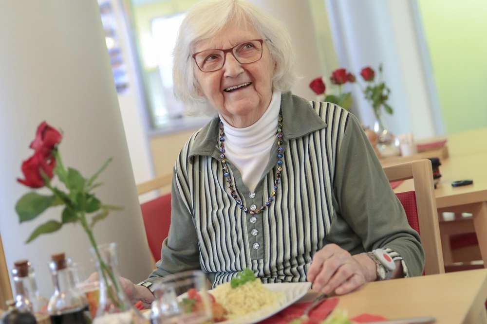 Eine ältere Frau mit Brille sitzt an einem Tisch und hat eine Mahlzeit vor sich. Auf dem Tisch steht eine Blumenvase.