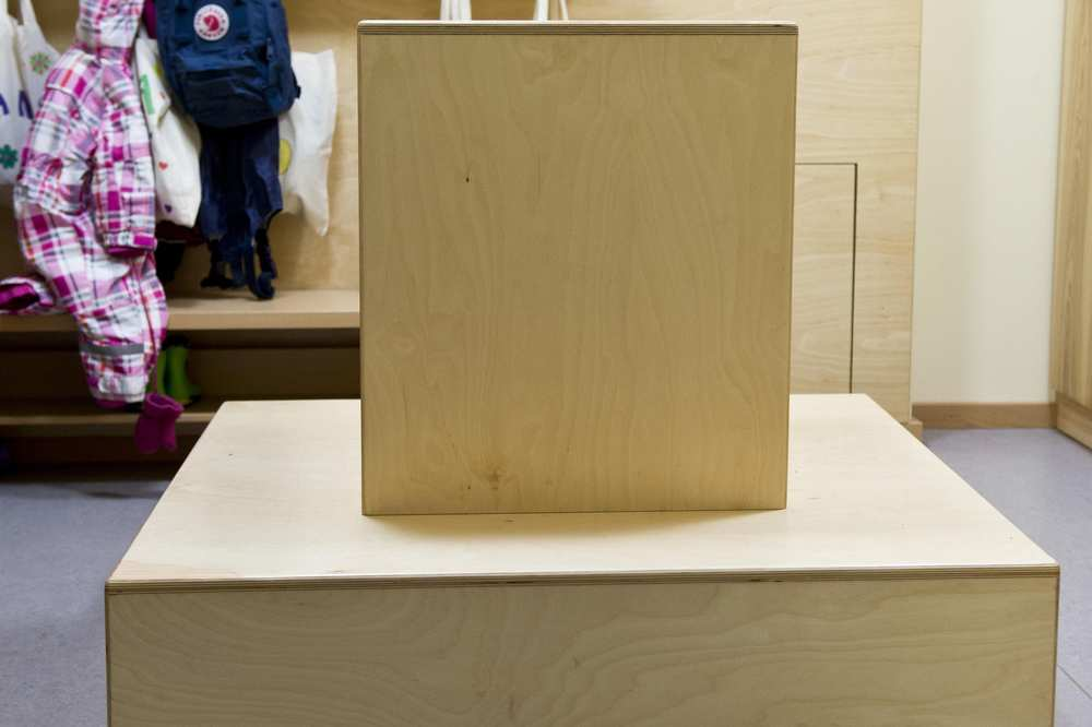 Eine quadratische Sitzfläche, in deren Mitte eine Rückenlehne ist.