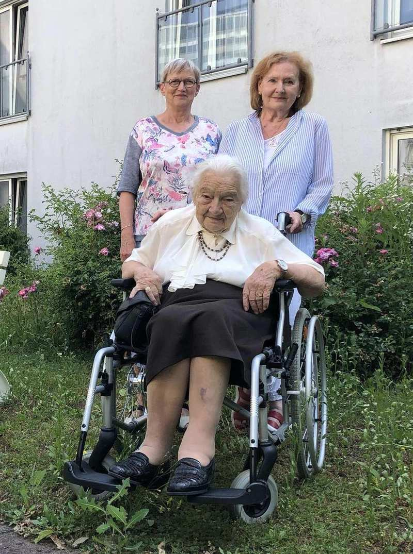 Drei ältere Frauen im Außenbereich der Diakonie Sophienstraße. Eine Frau im Rollstuhl, hinter ihr zwei weitere Frauen. Im Hintergrund die Grünanlage und Fensterfront des Pflegeheims.