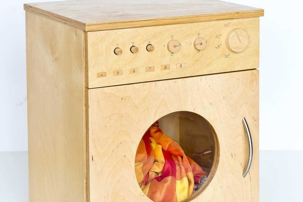 Eine Waschmaschine aus hellem Holz.