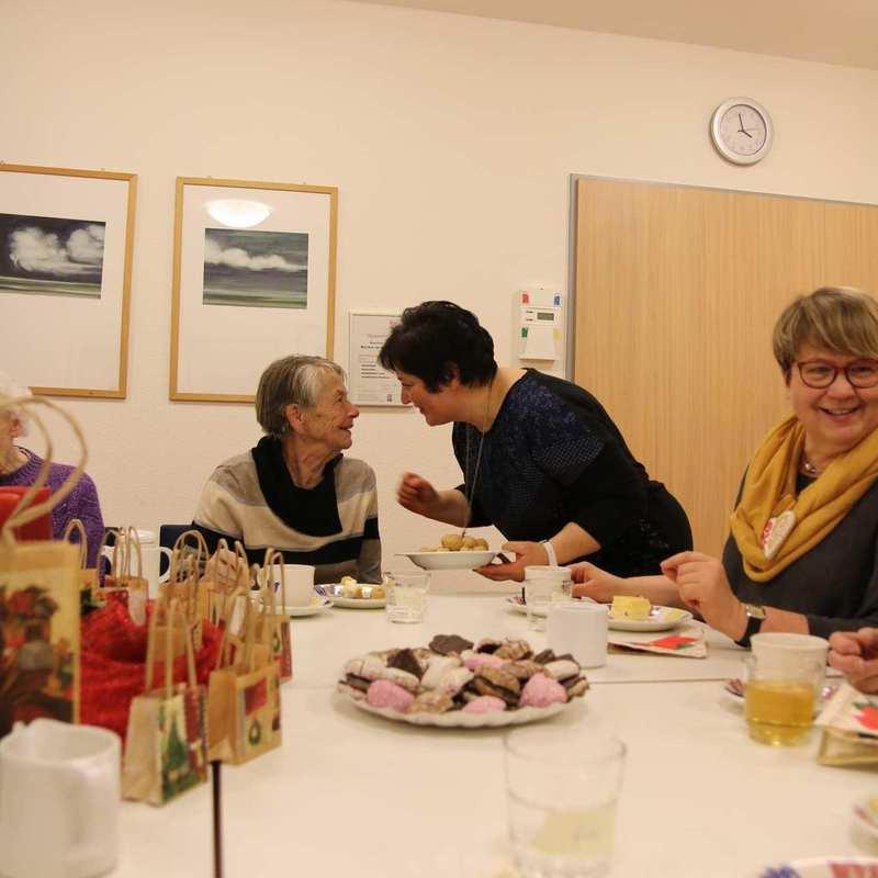 Mehrere Gäste und Helferinnen sitzen an einem reich gedeckten Weihnachtstisch.