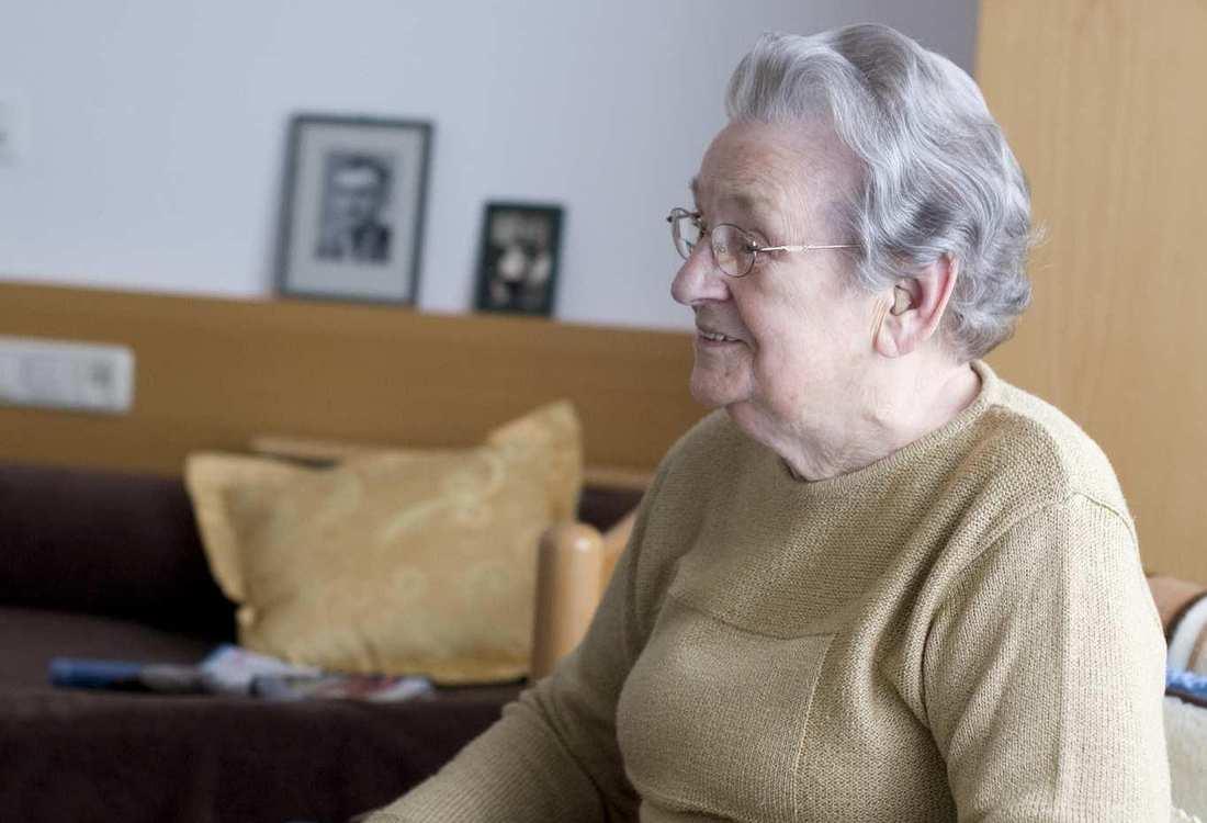 Eine ältere Frau sitzt in einem Sessel. Im Hintergrund ist ein Sofa mit Kissen.