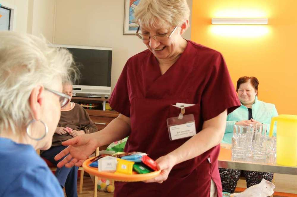 Eine Mitarbeiterin hält einer Bewohnerin ein Tablett mit buntverpackten Schokoladentafeln hin.