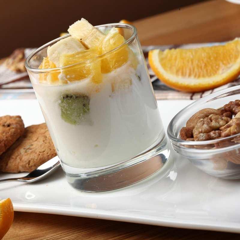 Ein Tablett, auf dem sich zwei Kekse, eine Müslischale und ein Joghurt mit Früchten befindet.