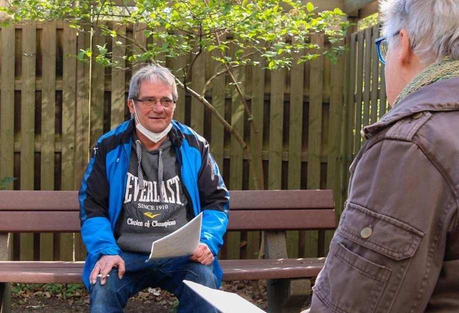 Ein Mann sitzt auf einer Bank und unterhält sich mit einer Frau.