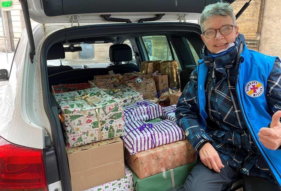 Eine Mitarbeitende der Bahnhofsmission sitzt in einem geöffneten Kofferaum eines Autos. Der Kofferaum ist mit verpackten Geschenken gefüllt.