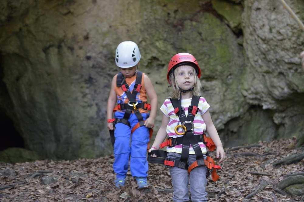 Zwei Kinder mit Klettergurten und Helmen vor einem Felsen in der Fränkischen Schweiz.