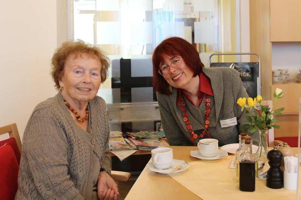 Zwei Frauen sitzen an einem Tisch und unterhalten sich. Auf dem Tisch stehen Kaffeegedecke und eine Vase mit Blumen.