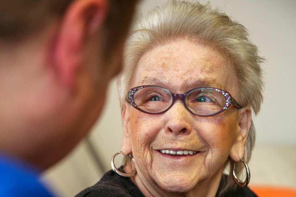 Eine ältere Frau mit Brille unterhält sich mit einer Pflegekraft.