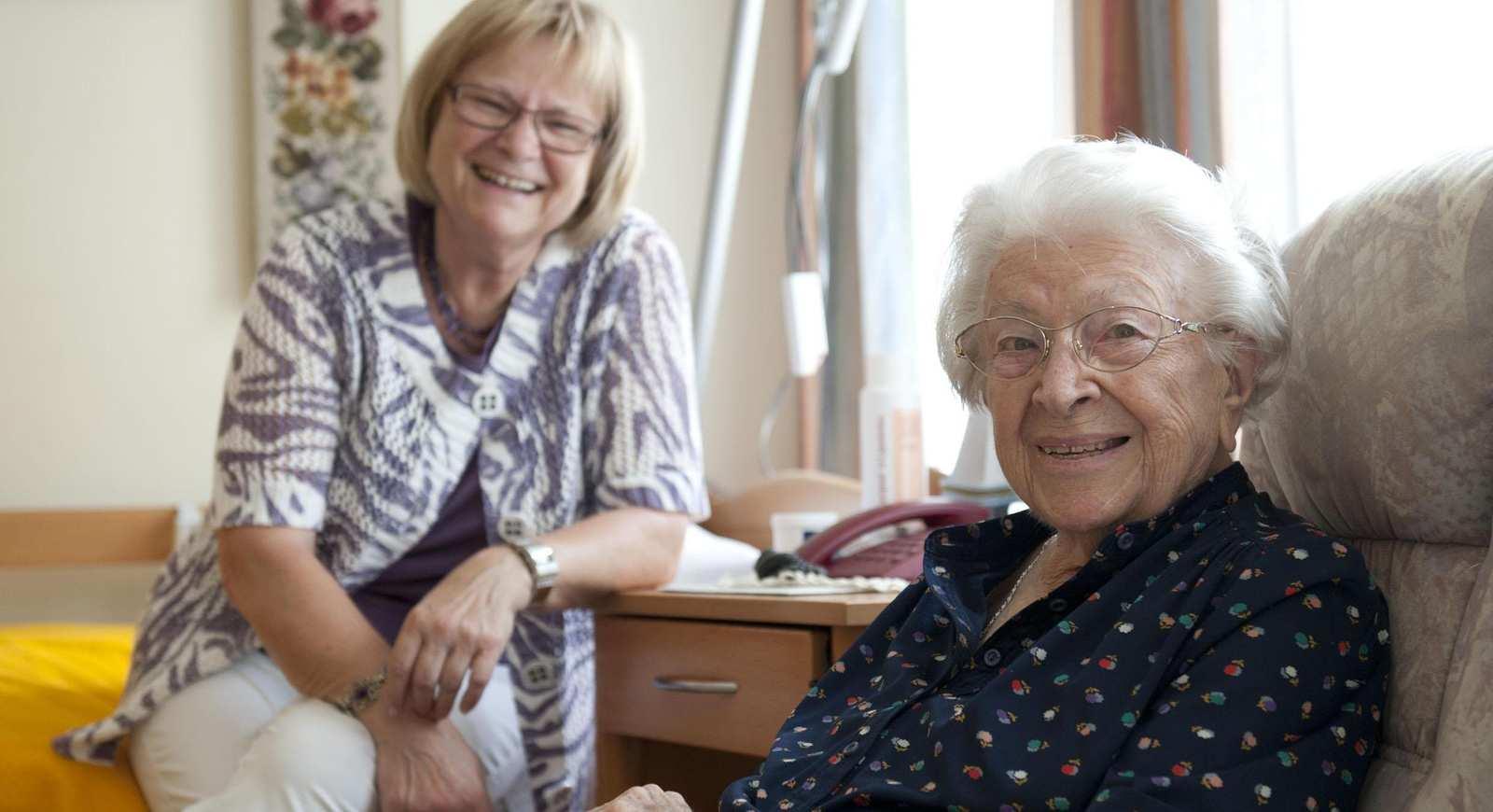 Zwei ältere Frauen mit Brillen sind in einem Wohnzimmer. Die eine Frau sitzt in einem Sessel, die andere neben ihr auf der Bettkannte.