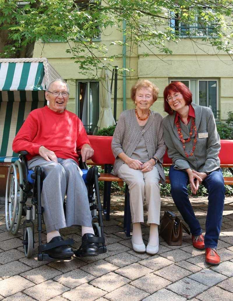 Ein Mann im Rollstuhl und zwei Frauen sitzen an bzw. auf einer Bank. Sie befinden sich auf einem gepflasterten Platz, im Hintergrund sind Bäume.