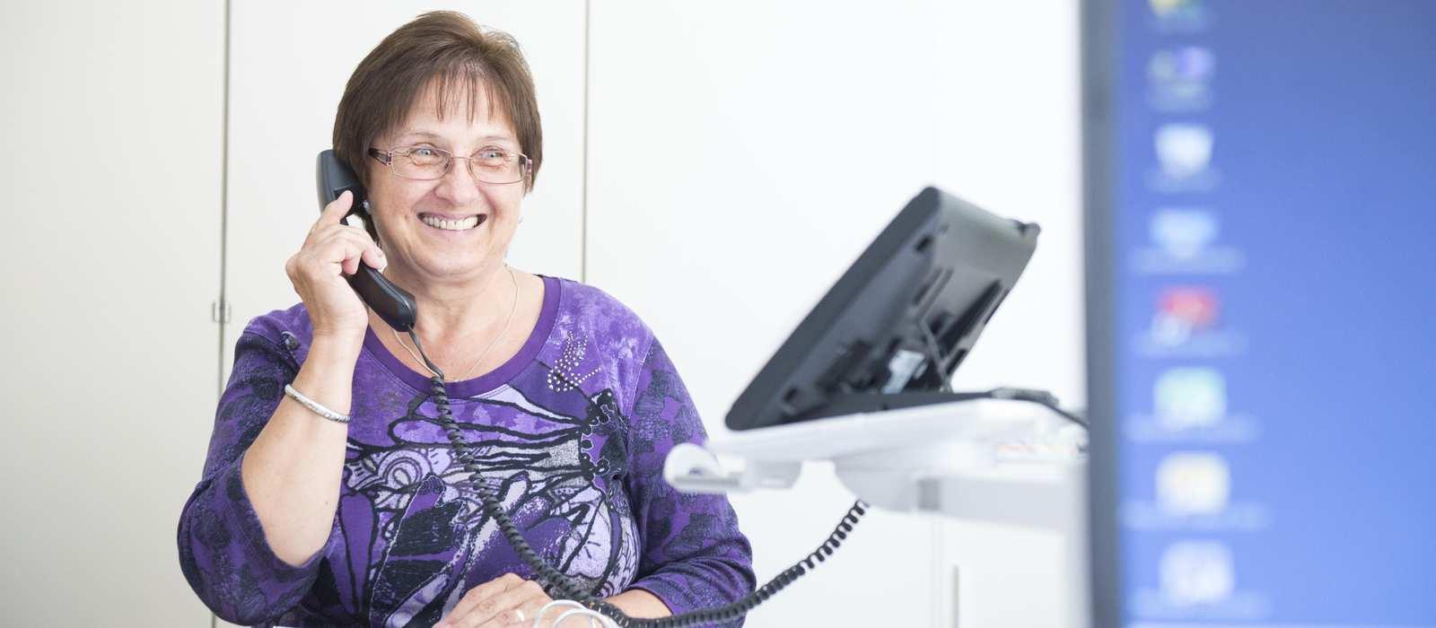 Eine Frau sitzt in einem Büro und telefoniert.