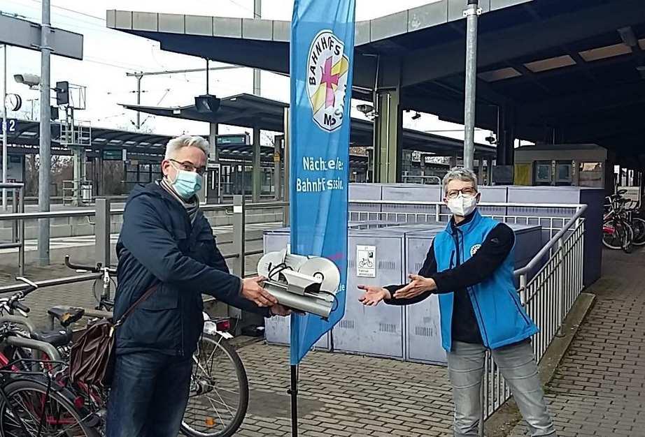 Ein älterer Mann überreicht einer Mitarbeiterin der Bahnhofsmission eine elektrische Brotschneidemaschine. Beide befinden sich am Bahnsteig des Erlanger Bahnhofes.