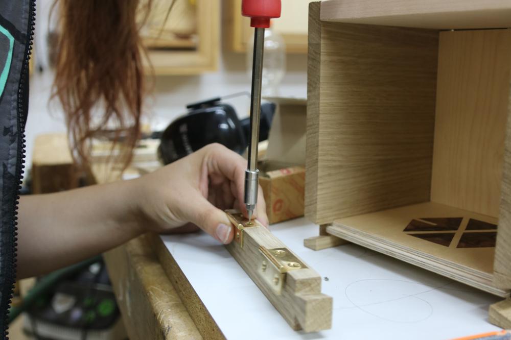 Eine Frau montiert ein Scharnier an einen Schrank.