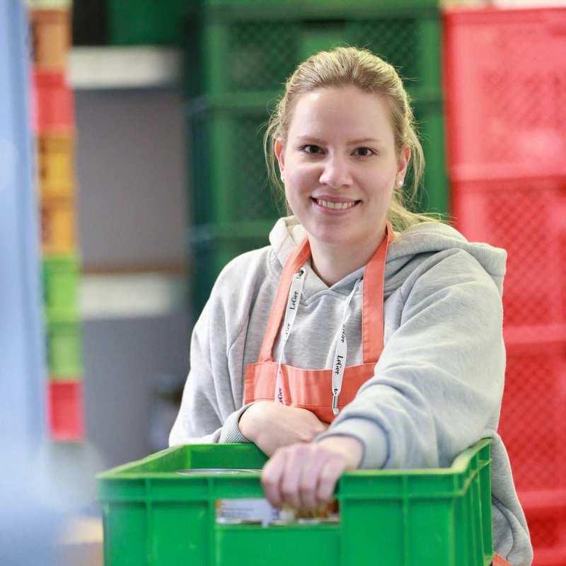 Eine junge Frau mit Tafel-Schürze greift nach einer Kiste