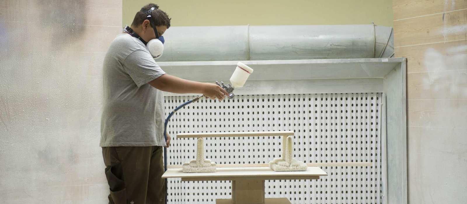 Ein Mann besprüht ein Werkstück mit Imprägniermittel. Er trägt eine Atemmaske.