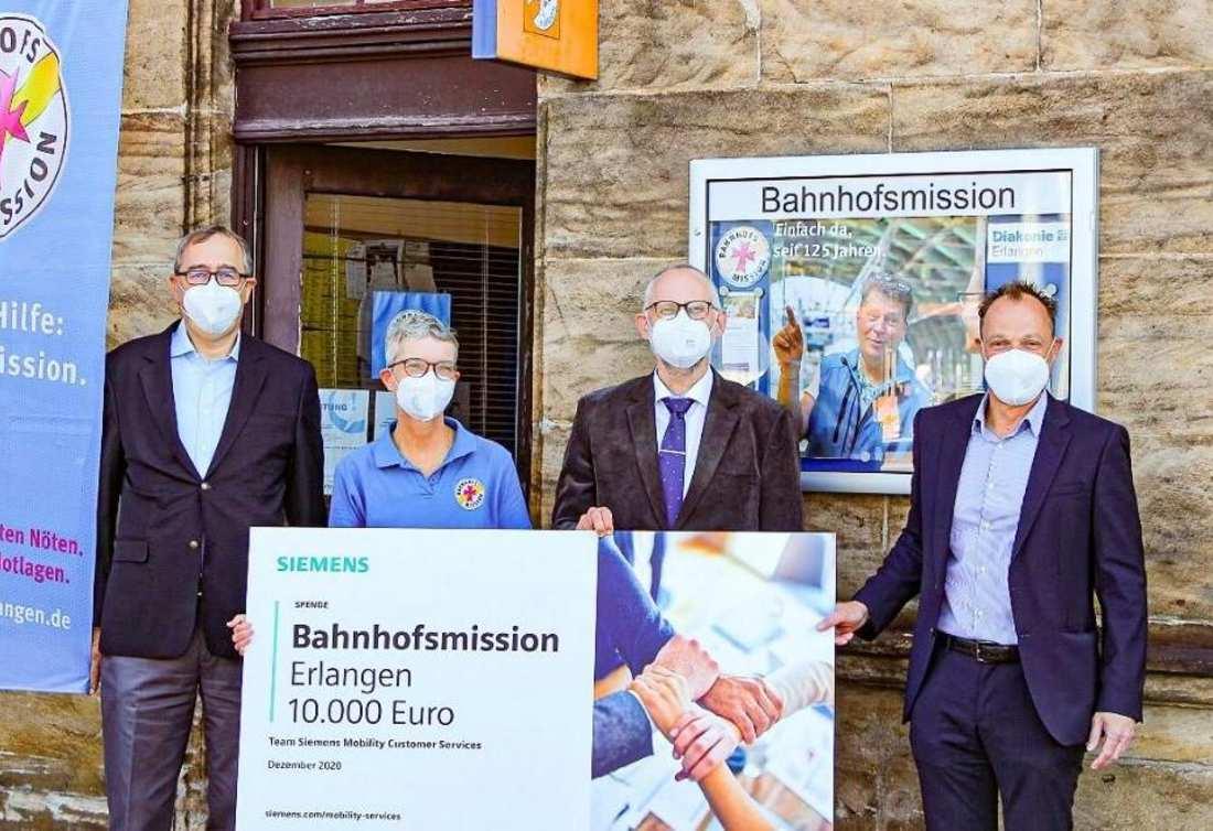 Siemensmitarbeitende übergeben den symbolischen Spendenscheck an die Bahnhofsmission Erlangen.