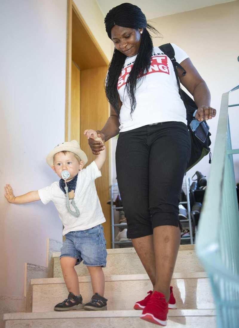 Eine Frau läuft mit einem kleinen Jungen an der Hand die Treppe runter.