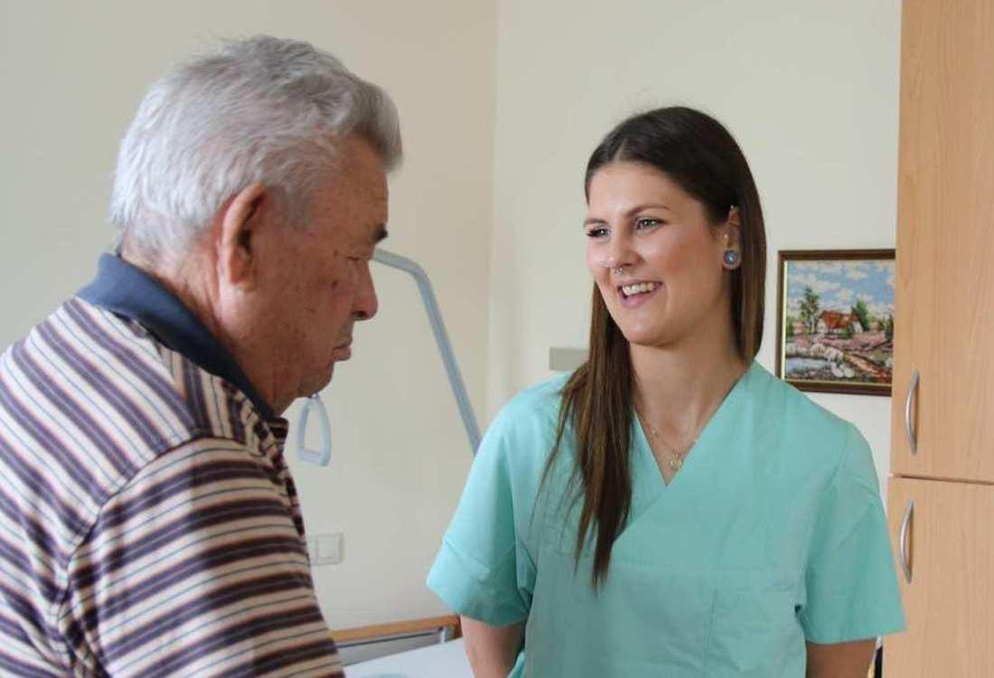 Eine Pflegekraft hört dem neben ihr stehenden Bewohner zu. Im Hintergrund des Zimmers ist ein Bett zu sehen.