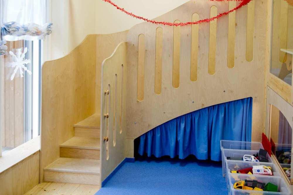 Eine geschwungene Holztreppe, die auf die erste Etage einer Spiellandschaft führt.