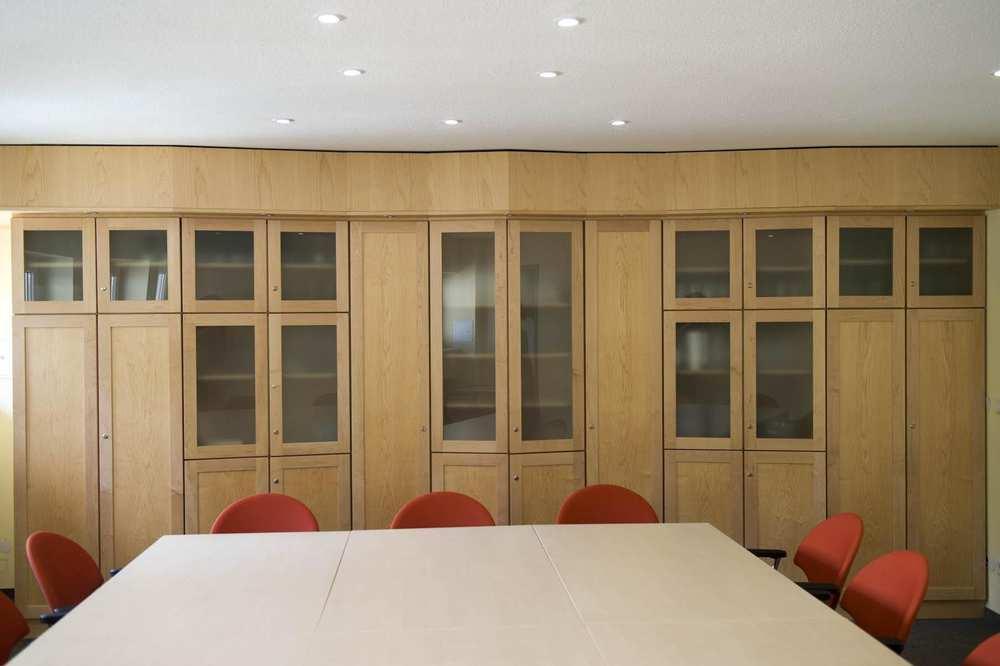 Eine komplette Inneneinrichtung, bestehend aus fünf miteinander verbundenen Wandschränken aus hellem Holz. Die Schranktüren sind zum Teil verglast.