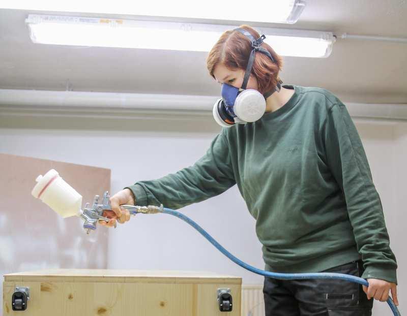 Eine Frau mit Luftfiltermaskte besprüht ein Werkstück mit einer Flüssigkeit.