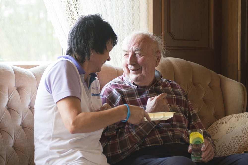 Eine Pflegekraft und eine zu betreuende Person sitzen in einem Wohnzimmer auf einem Sofa.