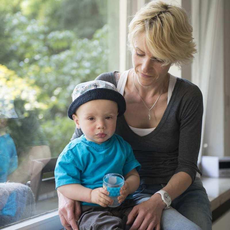 Eine junge Frau sitzt auf einer Fensterbank und hat ein Kleinkind neben sich. Im Hintergrund sind Bäume zu sehen.