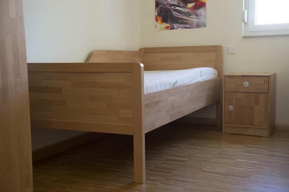 Ein Bett aus hellem Holz. An der Seite steht ein Nachtkästchen.