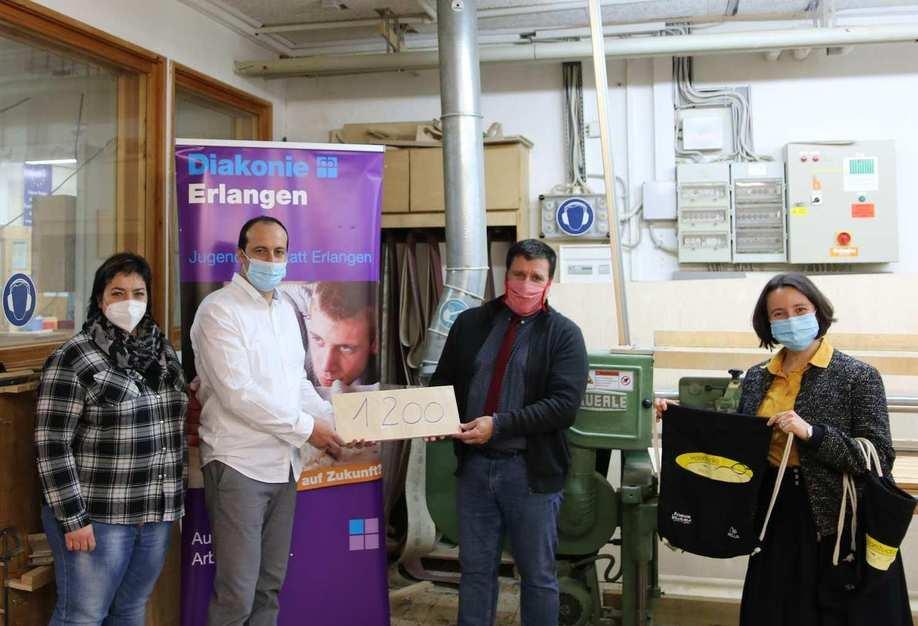 Vier Personen stehen in einem Werkstattraum und halten ein Holzschild mit der Zahl 1200 Euro.