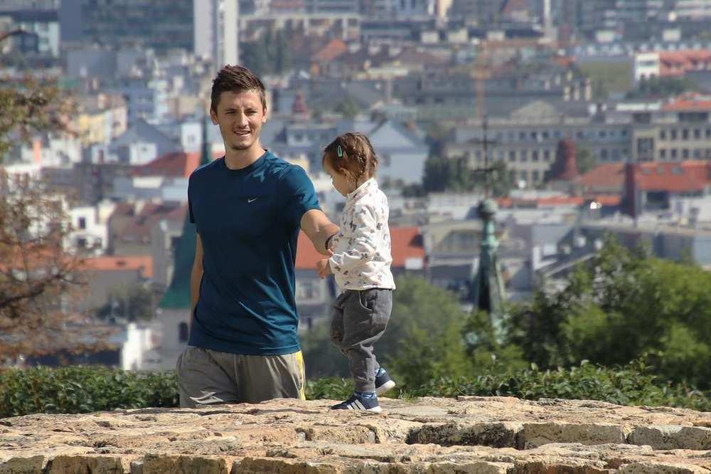 Ein junger Mann stützt ein Kleinkind, das auf einer Natursteinmauer läuft. Im Hintergrund sind Häuser einer Stadt.