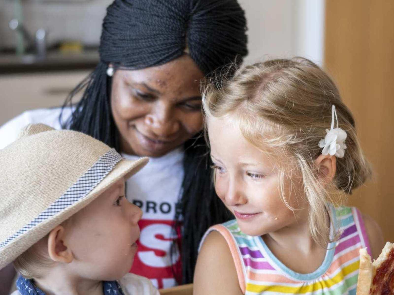 Eine Frau, ein kleiner junge und ein Mädchen sitzen am Tisch und lächeln sich an.