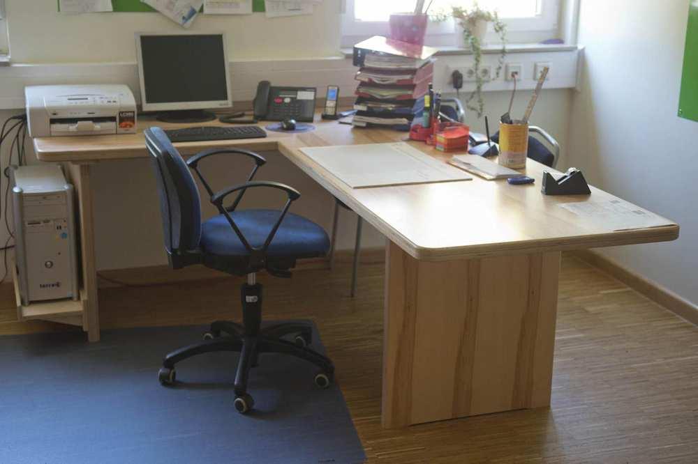 Eine L-förmige Schreibtischplatte mit einer Halterung für den PC-Tower aus hellem Holz.