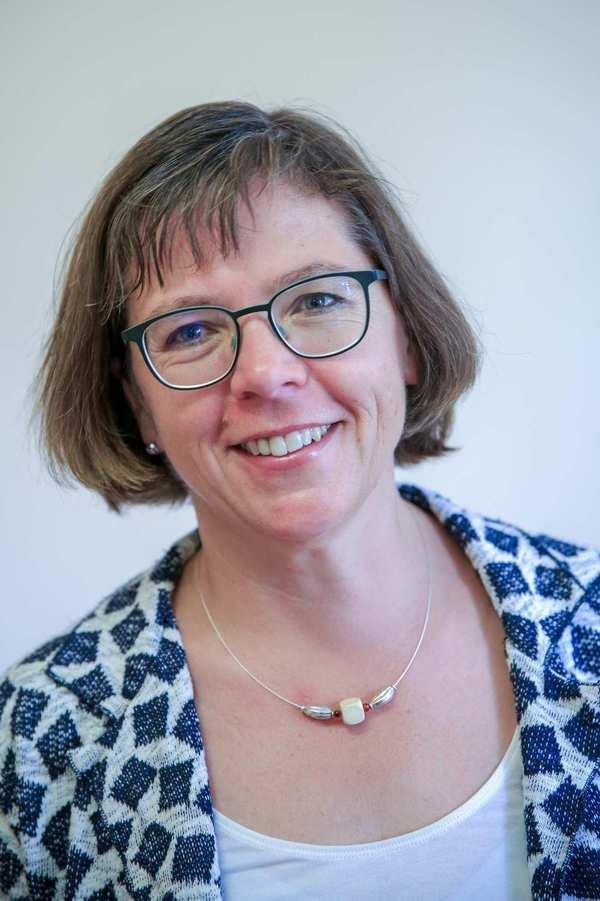 Elke Bollmann. Eine Frau mit schulterlangem dunkelbondem Haar und Brille.