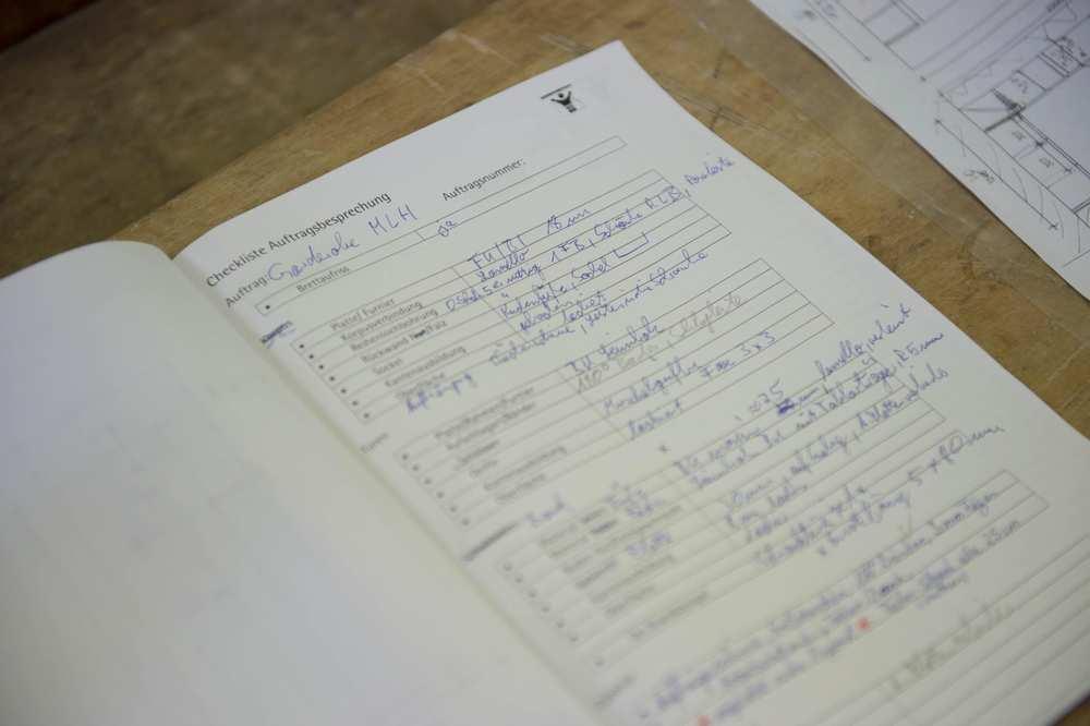 Ein handschriftlich ausgefülltes Blatt Papier. Es trägt die Überschrift Checkliste Auftragsbesprechung.