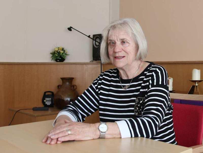 Eine ältere Frau sitzt an einem Tisch.