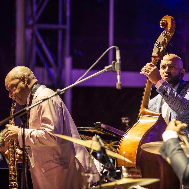 Drei Musiker in Anzügen. Sie spielen Saxophon, Kontrabass und Schlagzeug.