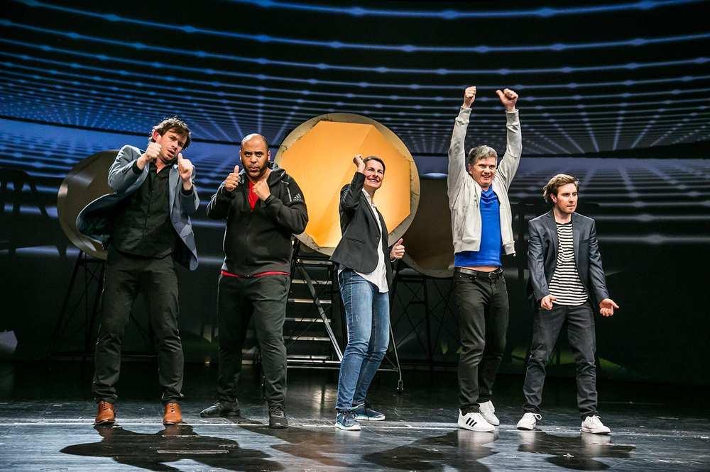 Fünf Jugendliche stehen auf einer Bühne. Sie sind im Dialog mit dem Publikum.