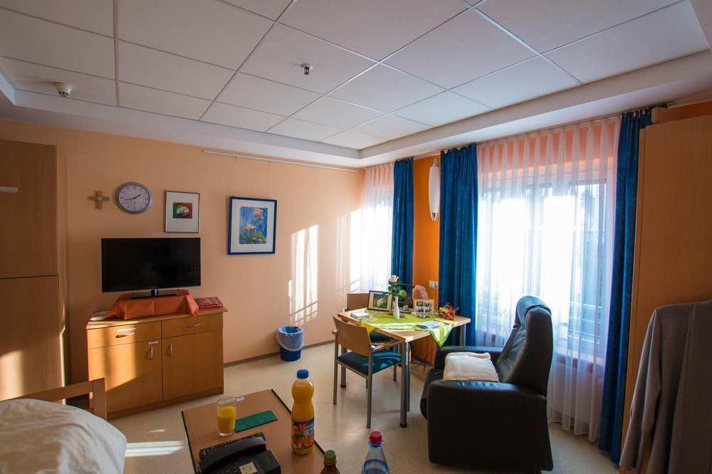 Ein geräumiges, helles Zimmer mit Sessel, Beistelltisch, Kommode und Fernseher.